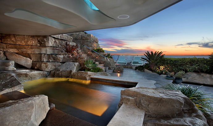 above The orientation of outside  terraces, which include a heated spa  and cold plunge, provides privacy.  1 The entry, with flowing creek, leads  to the living room and the view beyond