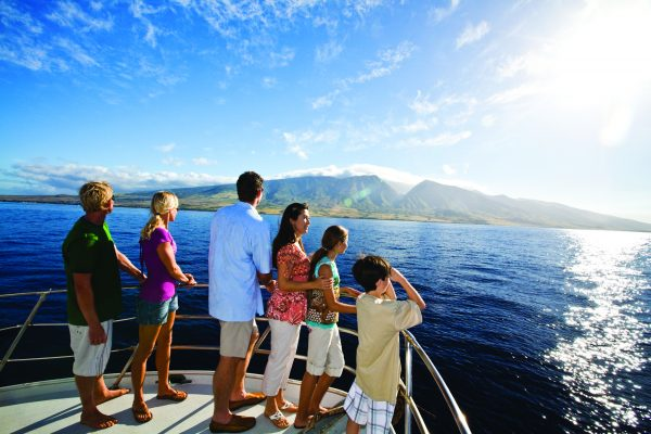 Group enjoying a boat trip with the west Maui mountains in the background