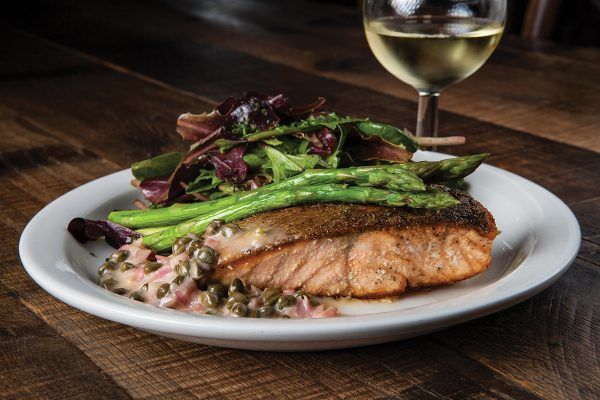 Sauteed filet of fresh salmon with asparagus and tender greens